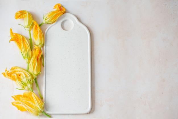 ホワイトボード上のズッキーニの花 Premium写真