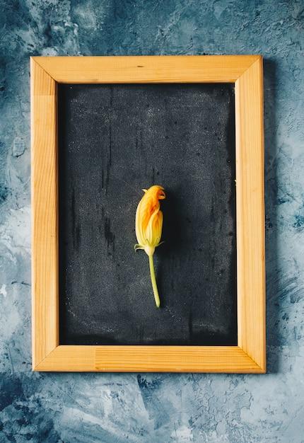 コンクリートの背景にザルでズッキーニの花 Premium写真