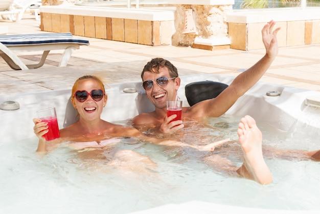 ジャグジープールでリラックスしている若いカップル 無料写真
