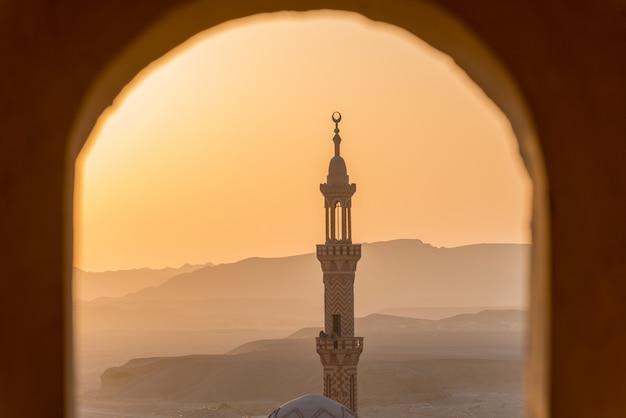 フォアグラウンドでイスラム教徒のモスクと砂漠に沈む夕日 Premium写真