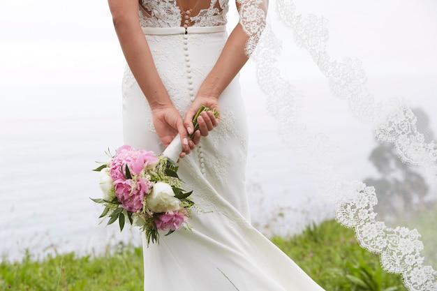 Невеста держит букет цветов у моря Premium Фотографии