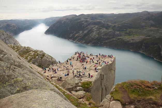Люди на вершине скалы преикестулен в норвегии Premium Фотографии