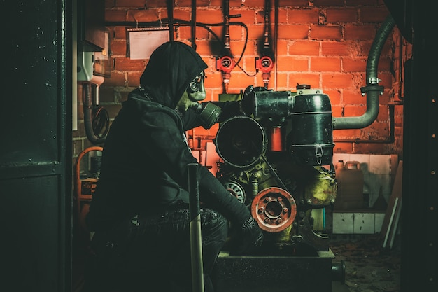 Человек с противогазом и молотком в машинном отделении. концепция ядерной, биологической и химической опасности. Premium Фотографии
