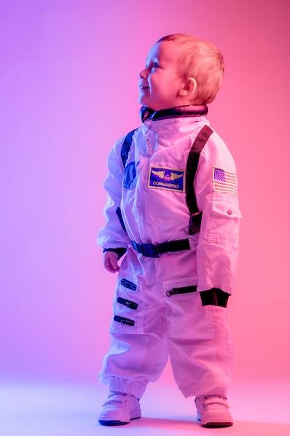 赤と青の光で照らされたアメリカの宇宙飛行士の服を着ている男の子のカラフルな肖像画。宇宙飛行士と子供の概念。 Premium写真