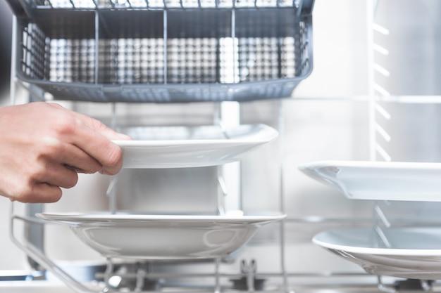 Крупным планом руки, удалив посуду в посудомоечной машине на кухне своей квартиры Premium Фотографии