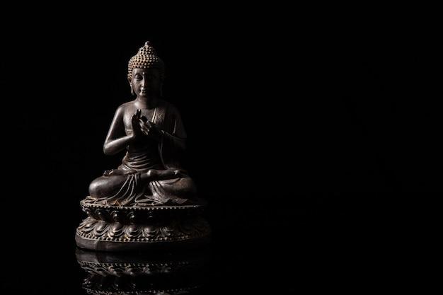 黒いコピースペースで瞑想に座っている仏の像 Premium写真