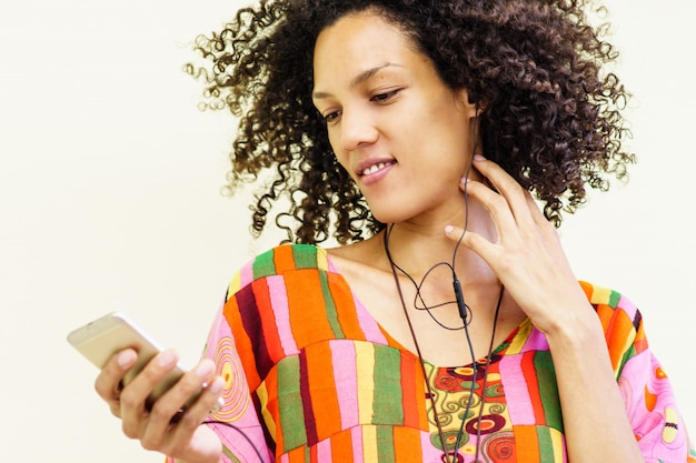 彼女の携帯電話で音楽を聴くと、ヘッドフォンを使用して女の子 無料写真