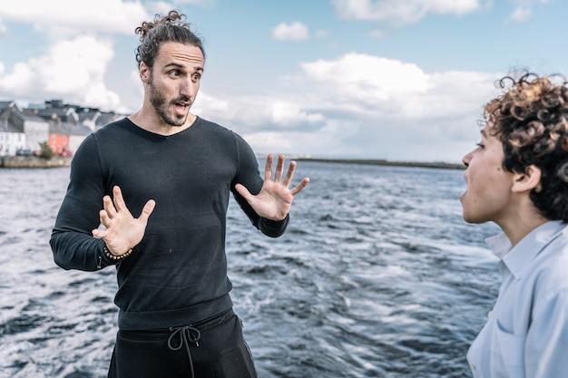 Молодая пара выразительно спорит с несосредоточенным морем Бесплатные Фотографии