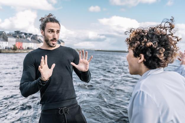 焦点の合っていない海と表情豊かに議論する若いカップル 無料写真
