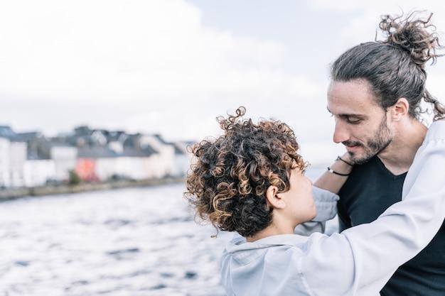 焦点が合っていない海と首でお互いをハグする若いカップル Premium写真