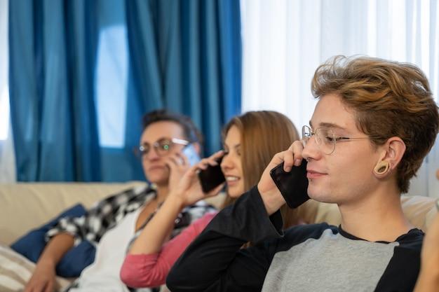 Группа молодых людей, сидящих в ряд на диване, разговаривают по мобильным телефонам Бесплатные Фотографии