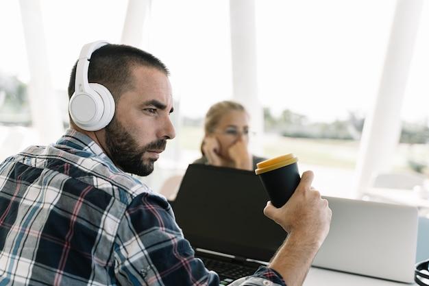 Бородатый мужчина с белыми касками и кофе в руке сидит перед ноутбуком в коворкинге Premium Фотографии