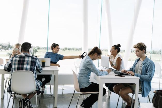 Группа людей, работающих за отдельными столами в коворкинге с ноутбуками, мобильными телефонами и кофе Premium Фотографии