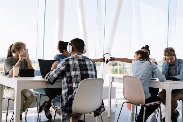 Две девушки в шлемах сидят за рабочим столом с другими людьми в коворкинге Premium Фотографии