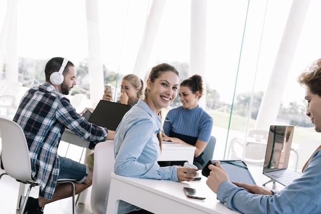 Молодая девушка с кофе в руке обернулась перед столом с другими людьми, работающими Premium Фотографии