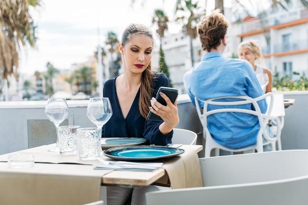 屋外レストランのテーブルに座って彼女の日付を待っている退屈な若い女の子 Premium写真