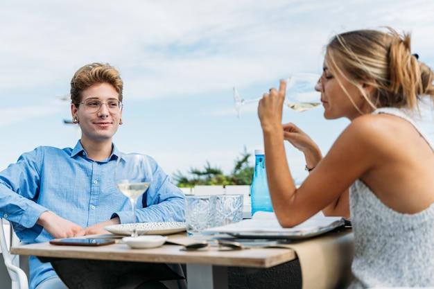 ビーチフロントのレストランのテーブルに座ってワインを飲む金髪の熟女を見て若い男 Premium写真