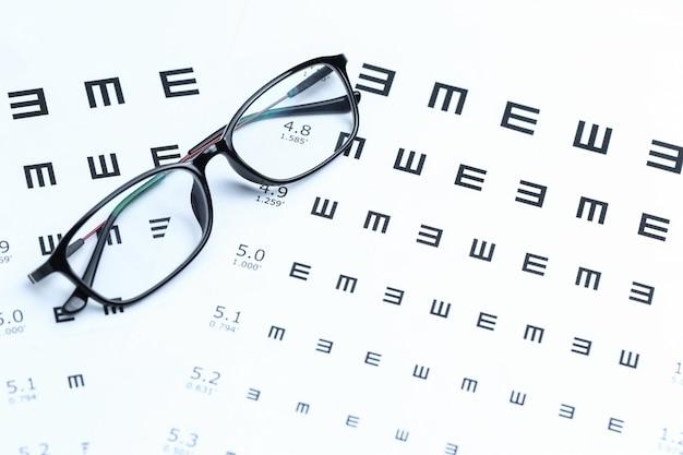 Очки и глазная диаграмма на белом фоне Бесплатные Фотографии