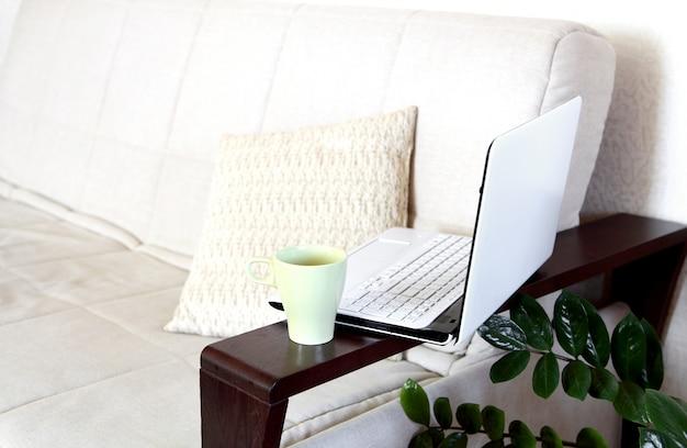 Ноутбук и чашка чая на диване. домашний офис. Premium Фотографии