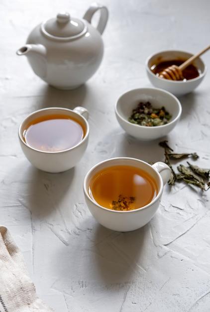 ティーポットとナプキンでテーブルに花の緑茶 Premium写真