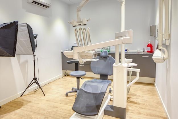 白い壁と木製の床を備えた、設備の整ったモダンな歯科医院ボックス Premium写真