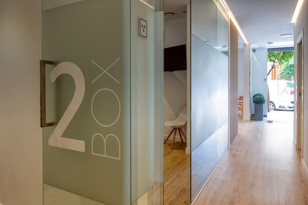 Полностью оборудованный современный зал стоматологической клиники с витражными картами и деревянными полами. Premium Фотографии
