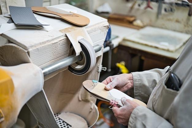 Профессиональный мастер по полировке, шлифованию и проверке ортопедических стелек в своей мастерской моделирует шаблоны с помощью токарного станка для тонкой наждачной бумаги. руки покрыты пылью. Premium Фотографии