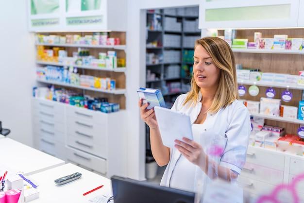 Молодой фармацевт держит таблетку и коробку с лекарствами. Premium Фотографии