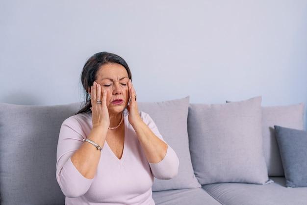 ストレスや痛みで顔をゆがめた頭痛に苦しんでいる女性 Premium写真