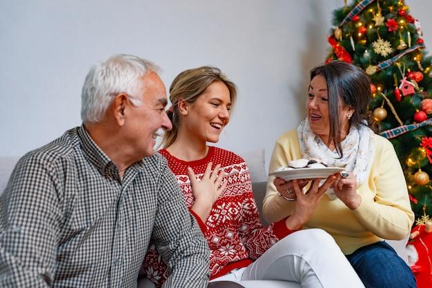 遊び心のある家族が自宅でジンジャーブレッドのクッキーを食べます。 Premium写真