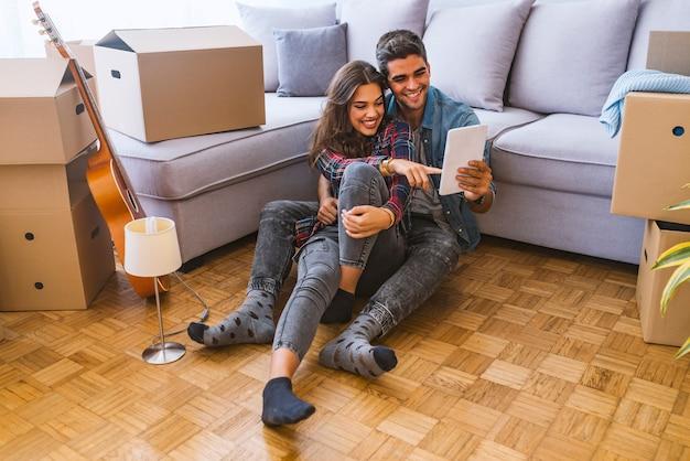 Вид сбоку молодая пара сидит на полу возле картонных коробок и просматривает современный ноутбук во время переезда в новую квартиру Premium Фотографии
