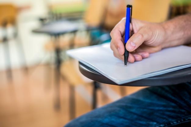 男は紙に書いている/署名している。ペンで手に集中 無料写真