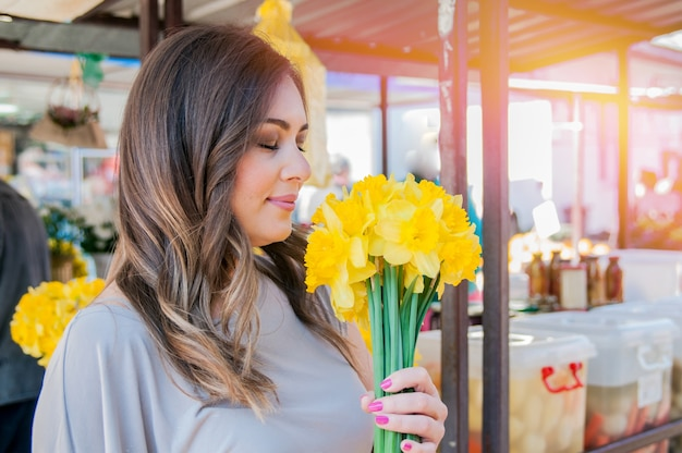 新鮮な花を選ぶ若い笑顔の女性。屋外の晴れた日に新鮮な花市場の屋台に立っている間に楽しんで花の花束を嗅ぐ美しい若い女性のプロフィールの肖像画を閉じます。 無料写真
