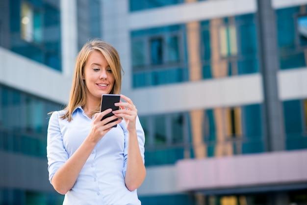 彼女のオフィスの前でスマートフォンで電話を聴く笑顔のビジネス女性 無料写真