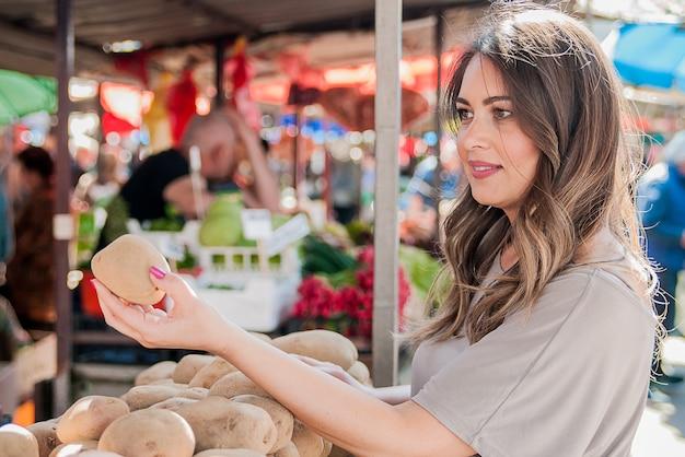 Довольно молодая женщина, покупая картофель на рынке. покупки, продажи, потребительство и концепция людей. женщина-покупатель, выбирающая свежий картофель из корзины на фермерском рынке Бесплатные Фотографии