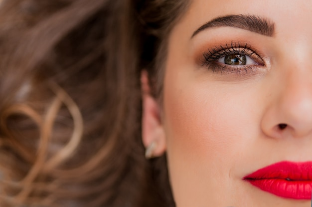 新鮮な毎日の化粧とロマンチックな波状の髪型を持つ美しい女性モデルの魅力的な肖像画。ファッション光沢のある蛍光灯、肌にセクシーな光沢のある唇のメイクとダークな眉毛 無料写真
