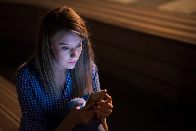 灰色の壁の背景に隔離された携帯電話を保持する不幸な女性を怒らせる。スマートフォンで悲しい探しの女の子のテキストメッセージ 無料写真