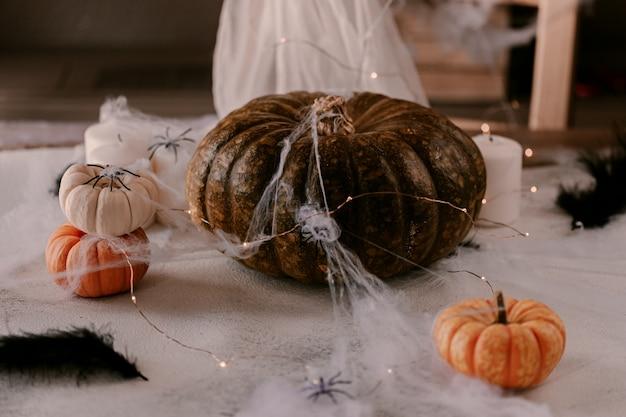 さまざまなカボチャ、光、クモと不気味なハロウィーンの装飾。 Premium写真