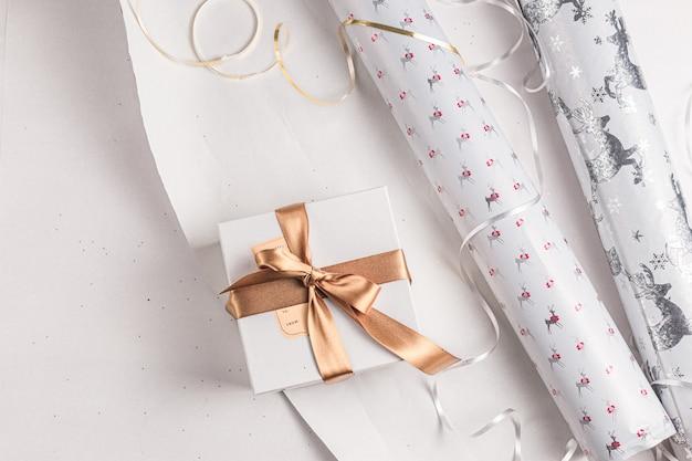 Подарочная упаковка. праздничная оберточная бумага на рождество. белые, золотые, серебряные праздничные цвета. курортный сезон. упаковка подарочной коробки ручной работы. Premium Фотографии
