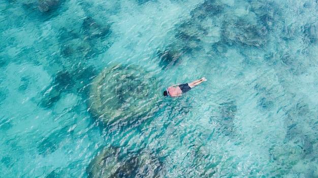 楽園の澄んだ水でシュノーケリングを泳ぐ休暇観光シュノーケル男。結晶水とサンゴ礁で少年シュノーケラーを泳ぎます。ターコイズブルーの海の背景。 Premium写真