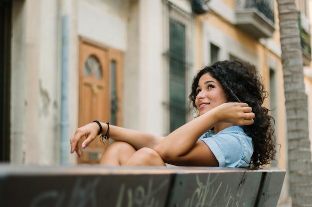 Вдумчивый девушка сидит на скамейке Premium Фотографии