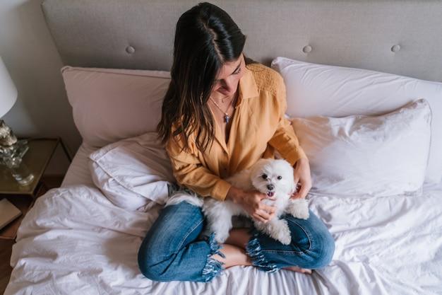 Женщина и ее милая собака дома пьют чай Premium Фотографии