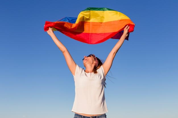 Женщина, держащая радужный флаг над голубым небом на открытом воздухе. Premium Фотографии