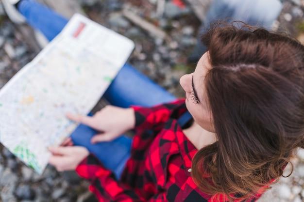 Взгляд сверху молодой красивой женщины используя или смотря карту. Premium Фотографии