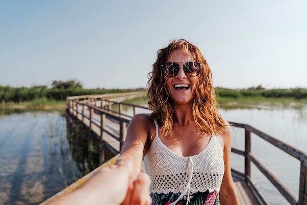Следуй за мной женщина в природном парке, держась за руку парня Premium Фотографии