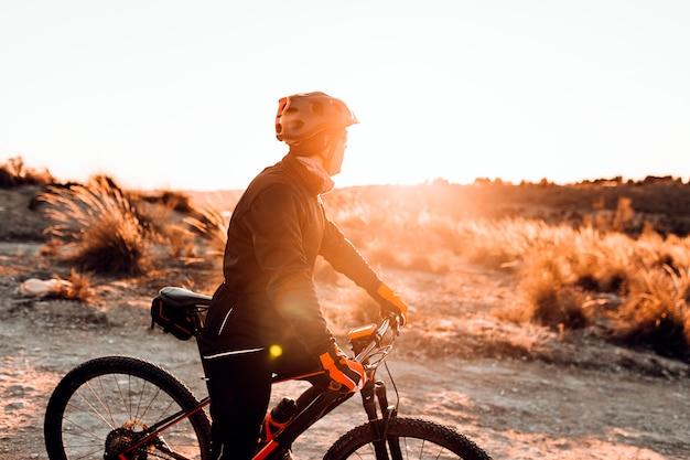 Велосипедист езда на велосипеде вниз скалистом холме на закате. концепция экстремального спорта. Premium Фотографии