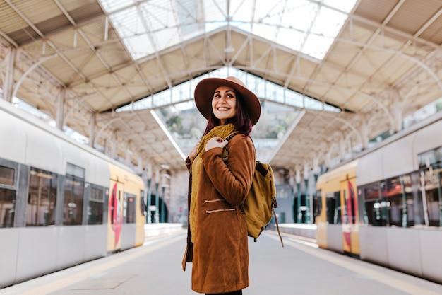 電車に乗ると旅行を待っている駅で若い観光客の女性 Premium写真