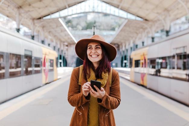 電車に乗って旅行を待っている駅で若い観光客の女性。携帯電話を使用して笑顔 Premium写真