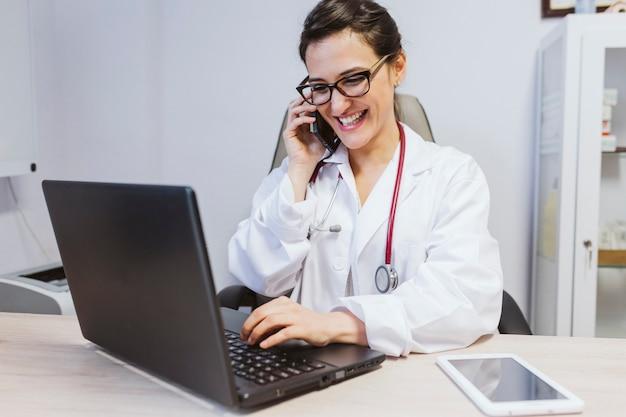若い医者は相談でラップトップに取り組んでいる女性。携帯電話で話しています。屋内での現代医療コンセプト Premium写真