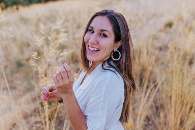黄色のフィールドで夕暮れ時の屋外で若い美しい白人女性の肖像画。幸福とライフスタイル Premium写真
